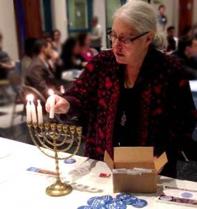 JCUA member Tina Escobar kindles the lights of Hanukkah at the JCUA member party.
