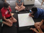 "On Monday morning, we examined root causes of injustice and learned community organizing skills. Here, Sarah, Gabi, and Emily work on a ""root causes tree"" for the issue of gun violence."