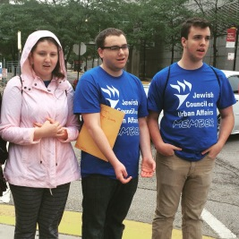 Leora, Jonah, and Brian lead the group in song and prayer outside the University of Chicago Medical Center.